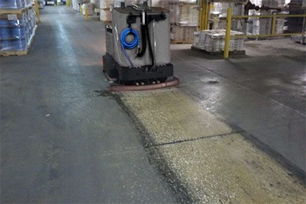 Factory Cat XR ride on scrubber cleaning dirty warehouse floor