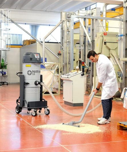 Nilfisk S3 vacuum collecting grain in food processing plant.